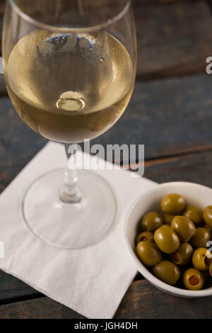 Close up of white wine by green olives served in container on wooden table against wall - Stock Photo