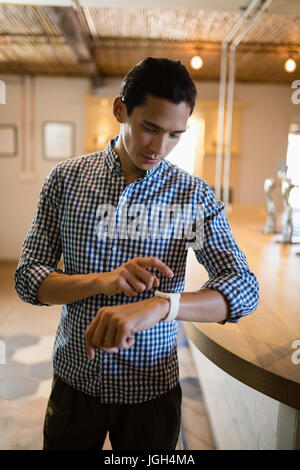 Man operating smartwatch at counter in restaurant - Stock Photo