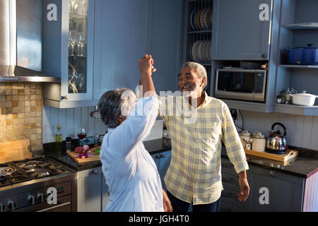 Smiling senior couple dancing in kitchen at home - Stock Photo