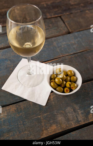 High angle view of white wine by green olives served in container on wooden table against wall - Stock Photo
