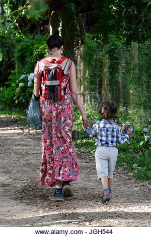 Mother and son holding hands walking on dirt road in the district of Maringá region also known as Visconde de Mauá, - Stock Photo