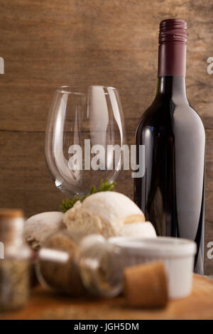Wine bottle by glass with spice and bread on table against wooden wall - Stock Photo