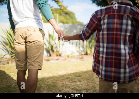 Midsection of father and son holding hands while standing in yard - Stock Photo