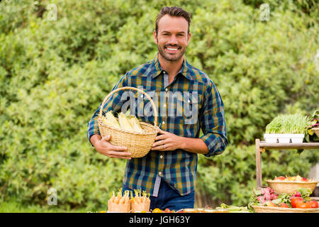 Portrait of happy young man selling organic vegetables at farm - Stock Photo