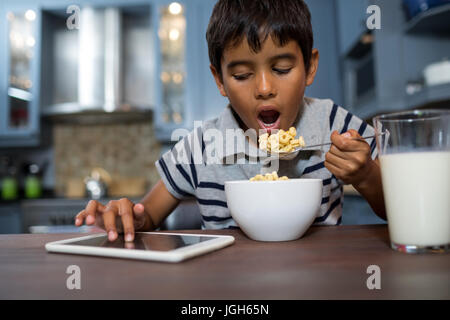 Close up of boy using tablet computer while having cereal breakfast at home - Stock Photo