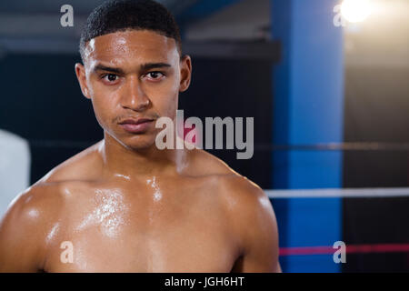 Portrait of confident young male boxer standing in boxing ring - Stock Photo