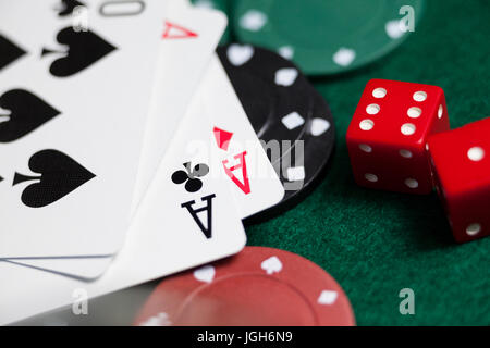 Close-up of playing cards, dices and casino chips on poker table - Stock Photo