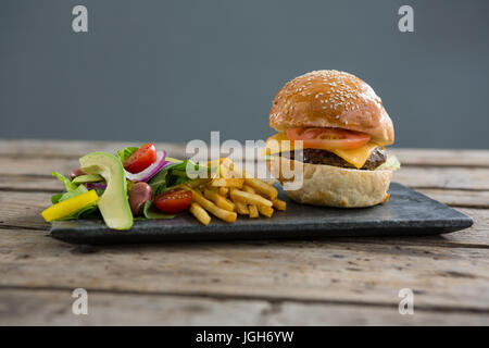 Salad with french fries and burger on slate at table against wall - Stock Photo