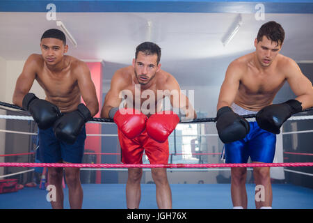Tired young male boxers leaning on rope in boxing ring - Stock Photo