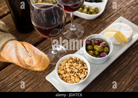 Close-up of marinated olives with glasses of wine on table - Stock Photo