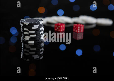 Close-up of chips stacks and dices on table at casino - Stock Photo
