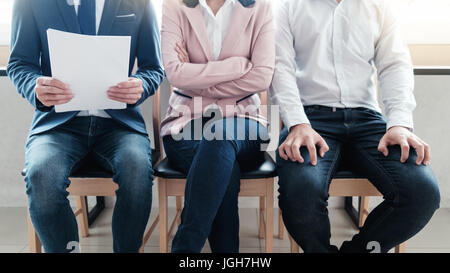 Line of young business people  sitting waiting for their turn for interview - Stock Photo