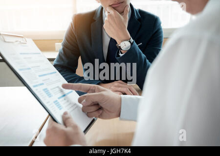 business man interviewer looking skeptical while listening to an asian female interview - Stock Photo