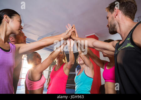 Low angle view of young athletes giving high-fives at fitness studio - Stock Photo