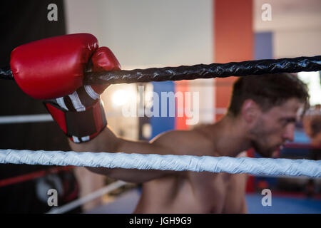 Side view of tired male boxer holding rope in boxing ring - Stock Photo