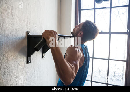 Side view of male athlete practicing pull ups on bar by window at fitness studio - Stock Photo