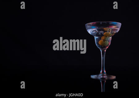 Close-up of cocktail martini with olives on table against black background - Stock Photo