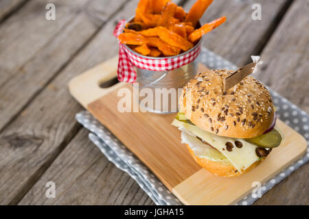Close up of french fries in container by cheeseburger on cutting board - Stock Photo