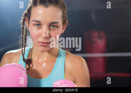Close-up portrait of young female boxer in boxing ring - Stock Photo