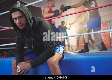 Portrait of young male boxer sitting on boxing ring while athletes practicing at fitness studio - Stock Photo