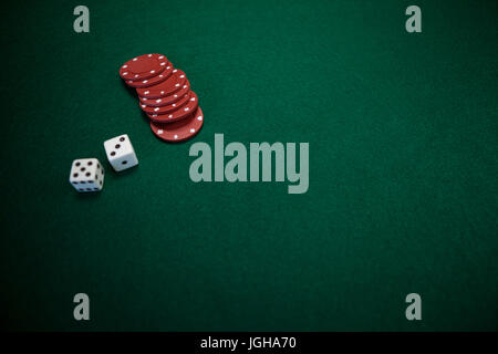 Pair of dice and casino chips on poker table in casino - Stock Photo