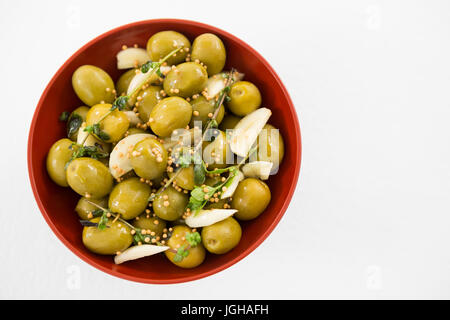 Close-up of marinated olives with garlic and herbs in bowl - Stock Photo