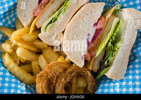 Close up of sliced burger with French fries and onion rings in container - Stock Photo