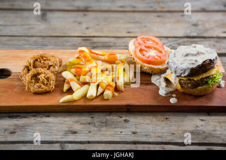 High angle view of French fries with sauce by onion rings and burger on cutting board - Stock Photo