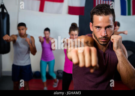 Portrait of young male practicing boxing against flags in fitness studio - Stock Photo