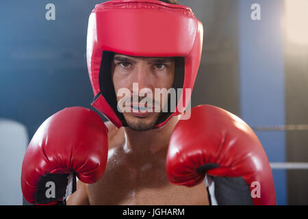 Close-up portrait of confident male boxer wearing red headgear and gloves in boxing ring - Stock Photo