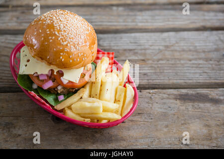 Cheeseburger and French fries in red basket on wooden table - Stock Photo