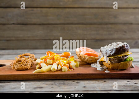 Close up of French fries with sauce and burger and onion rings on cutting board - Stock Photo