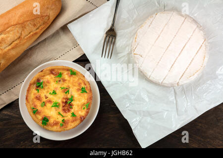 An overhead photo of French food products with a place for text. A baguette, a quiche, and a head of Camembert cheese, - Stock Photo