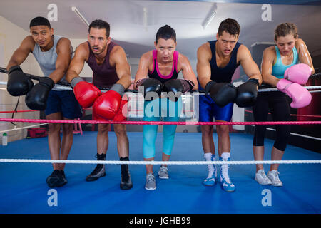 Exhausted young boxers leaning on rope in boxing ring - Stock Photo
