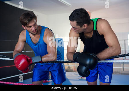 Young male boxers leaning on boxing ring rope - Stock Photo