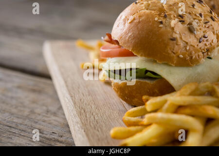 Close up of cheeseburger with french fries served on cutting board - Stock Photo