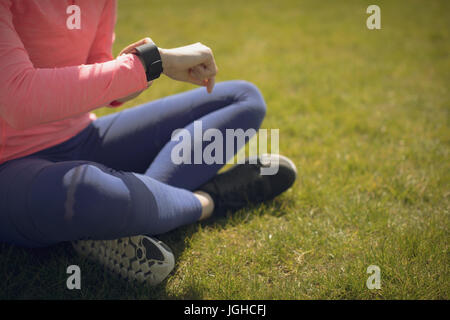 Low section of athlete checking time while sitting on grassy field - Stock Photo
