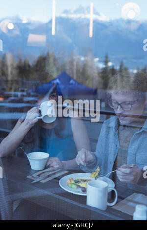 Couple having breakfast in the kitchen at home - Stock Photo