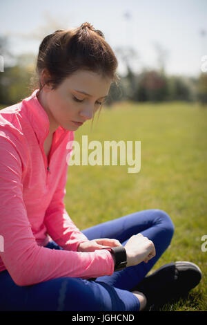 Female athlete checking time while sitting on grassy field - Stock Photo