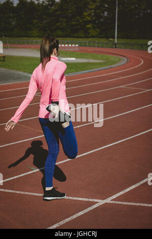 Rear view of female athlete stretching leg on running track during sunny day - Stock Photo