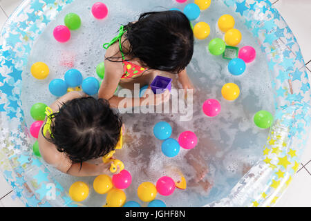 Asian Chinese little sisters playing in the inflatable pool inside the house. - Stock Photo