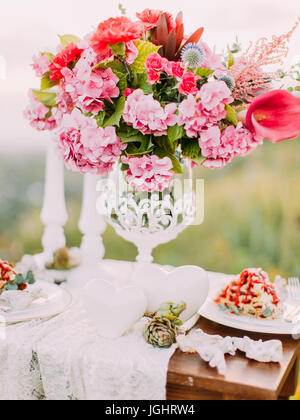 The close-up view of the vase of beautiful colourful peonies placed on the wedding table in the mountains. - Stock Photo