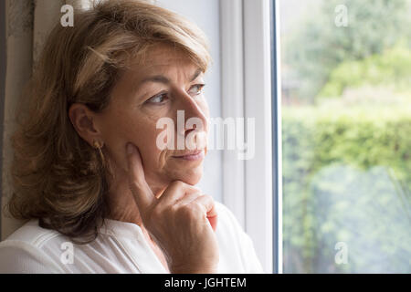 Sad Woman Suffering From Agoraphobia Looking Out Of Window - Stock Photo