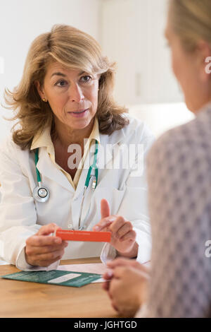 Female Doctor Discussing Medication With Patient - Stock Photo