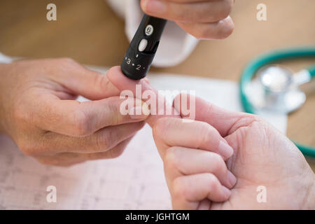 Doctor In Surgery Checking Blood Sugar Level - Stock Photo