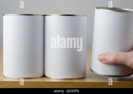 Conceptual image of three tin cans with blank white paper labels on a shelf, with middle aged female hand reaching - Stock Photo
