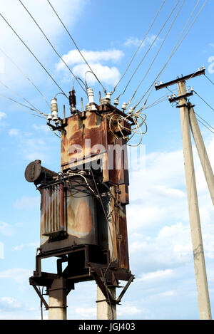 Aged and rusting sub power station with electricity cables and a pylon in the background - Stock Photo