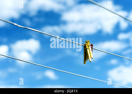 Three brightly colored plastic clothes pegs on a  family washing line with blue sky and white summer clouds in the - Stock Photo