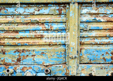 Old corroded blue metal with rust flecks and peeling damaged paintwork - Stock Photo