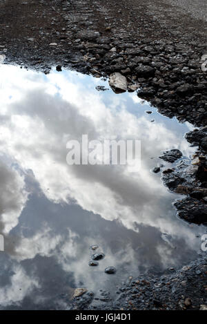 Cracked and broken asphalt pothole on the surface of a crumbling road. Rain water puddle collects in the cracked - Stock Photo